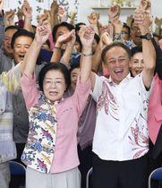 那覇市長選で再選を決め、支援者らと万歳する城間幹子氏。右は玉城デニー沖縄県知事=21日夜、那覇市