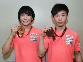 【アジアカデット選手権で獲得した金メダルを掲げる藤波選手(左)と銅メダルを掲げる弓矢選手=いなべ市のいなべ総合高校で】
