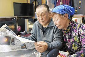 強制不妊問題に関する新聞記事を読む小島喜久夫さんと妻の麗子さん=22日、札幌市北区で