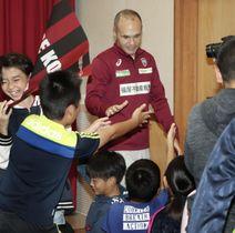 神戸市立だいち小を訪れ、児童とタッチを交わすイニエスタ選手=17日