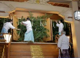 サカキで覆った本殿の扉にしめ縄を張る神職=加古川市加古川町大野、日岡神社