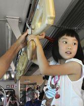 三陸鉄道リアス線の車内にラグビーボールを模した楕円球形のつり革を取り付ける地元の子ども=17日午前、岩手県宮古市