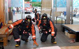 【室内に進入し消火活動の実演をする消防職員ら=亀山市関町小野の「亀寿苑 関ディアップセンター」で】