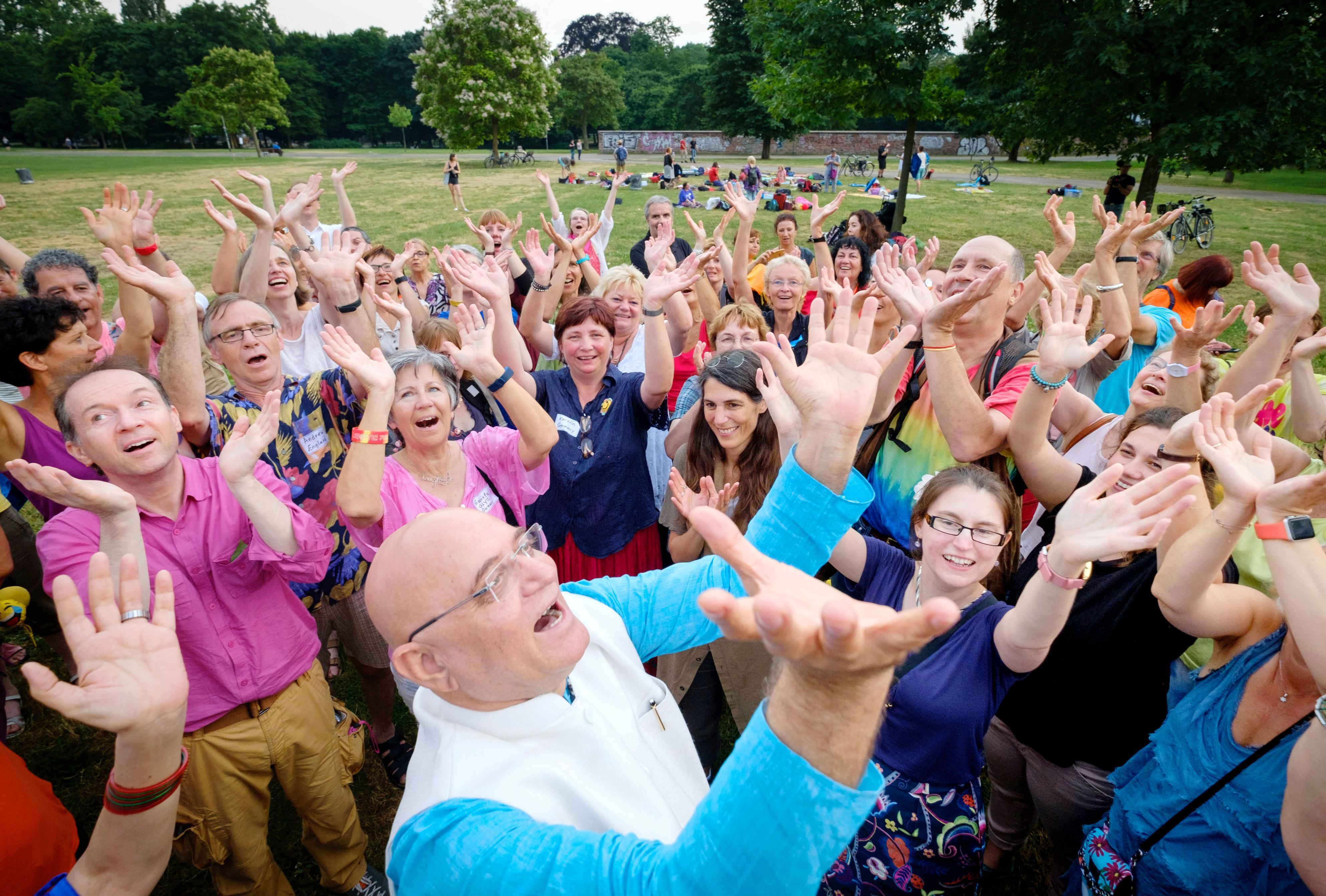 ドイツ・フランクフルトで開かれた「笑いヨガ」の初の世界大会。公園でインド人医師マダン・カタリア(手前)が両手を上げて実演すると、笑いの渦が広がっていく(撮影トマス・ローネス、共同)