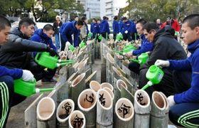神港学園の部員とボランティア活動に取り組む北原光広前監督(右から2人目)と長男直也監督(左から2人目)=16日午後、神戸市中央区の東遊園地