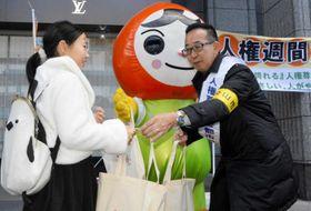 買い物客らにエコバッグを手渡す松山市職員