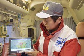 AIによる病人やけが人の発生予測結果を示すタブレット端末を手にする救急隊員=11日午後、名古屋市中区