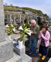 先祖の墓に手を合わせる墓参者=鹿児島市の唐湊墓地