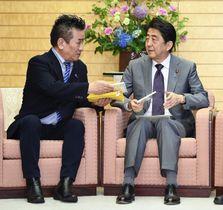 歌手のBOROさん(左)からCDを受け取る安倍首相=23日午後、首相官邸