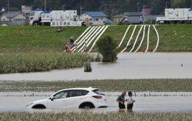 いまだに水で覆われた畑。ポンプ車で藤井川への排水作業が進められた=15日午後12時58分、水戸市飯富町、菊地克仁撮影