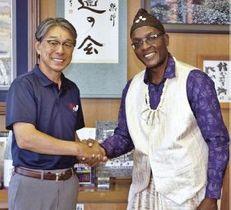 真砂充敏市長(左)と握手を交わすカメルーンバレーボール連盟のトッコ・エカンビ・オーガスト・エマニュエルさん=9日、和歌山県田辺市長室で