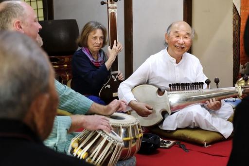 祖父の位牌が納まる愛媛県・佐島の西方寺の本堂で、弦楽器サロードを演奏するスティーブ・オダ(右)。親戚の小田重文(左手前)ら島民が聞き入った=19年4月