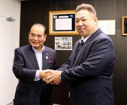 天満市長(左)と握手を交わす九重親方