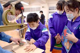 高校生に教わり、電動糸のこで板を切る児童=多度津町本通、多度津高