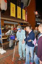 アイマスクを着けるなどして居酒屋から避難する参加者ら=12日午後7時すぎ、横浜市中区