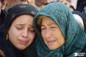 結婚から10日もせずにトルコ軍側の攻撃で夫を失った女性(左)。葬儀で夫の遺体を前に義母と寄り添っていた=2018年2月12日、シリア北西部アフリン(共同)