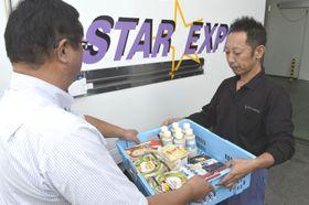 ハローズから回収した食品を福祉施設の担当者に渡すスター急便の社員(右)=徳島市東沖洲1
