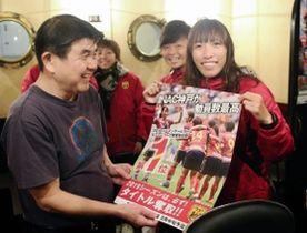1年の感謝を込めた特製ポスターを手渡すINAC神戸の中島主将(右)=神戸市内