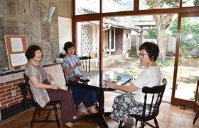 古民家「旧依田四郎邸」を改装してオープンしたカフェ「浜丁」。窓際に座り、来店者が会話を弾ませている=松崎町松崎