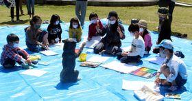 彫刻作品を前に、はしもとさん(左から6人目)からスケッチの指導を受ける子どもたち
