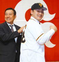 入団会見で背番号「8」を披露する巨人の丸。左は原監督=東京都千代田区で