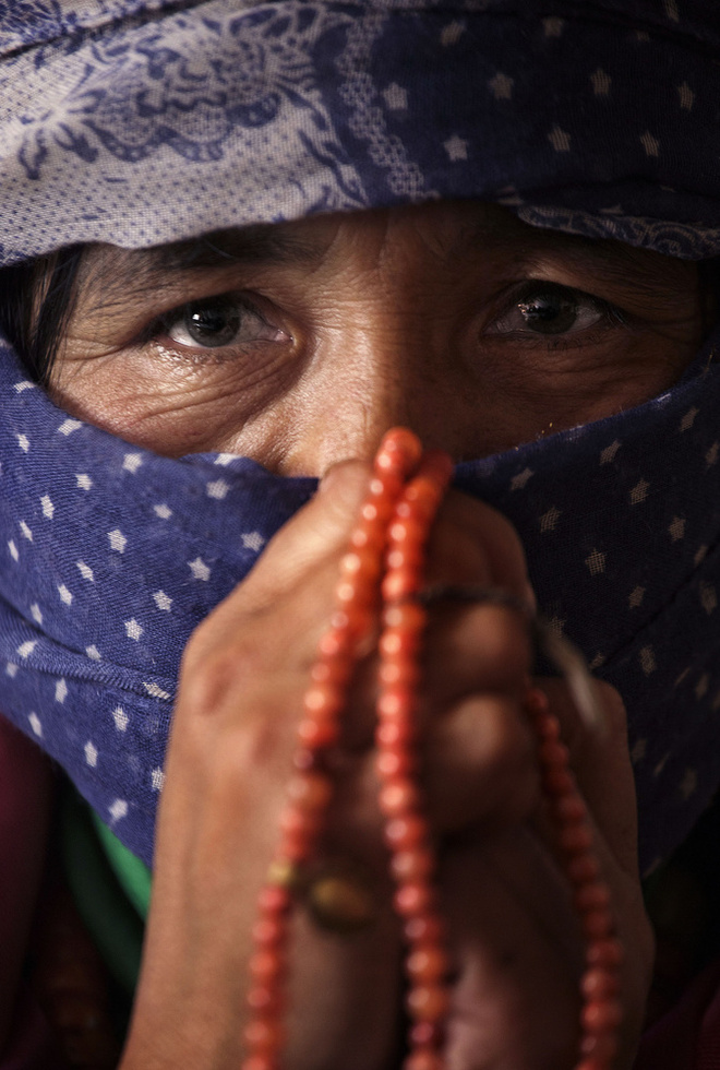 娘ツェリン・キの形見の首飾りを握る母ドルマ。19歳の学生だったツェリン・キは、2012年、中国政府のチベット抑圧に抗議し焼身した=中国・甘粛省(撮影・高橋邦典、共同)