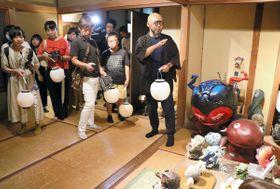 プレスツアーで柳生さん(右端)の説明を受けながら妖怪美術館の展示作品を見て回る報道関係者ら=土庄町