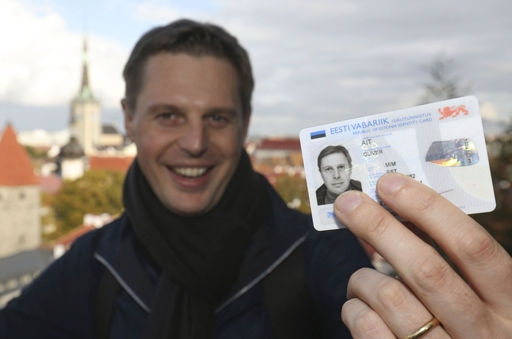 個人識別番号と電子チップが埋め込まれたIDカードを手にするオリバー・アイト=2019年9月、エストニア・タリン(共同)