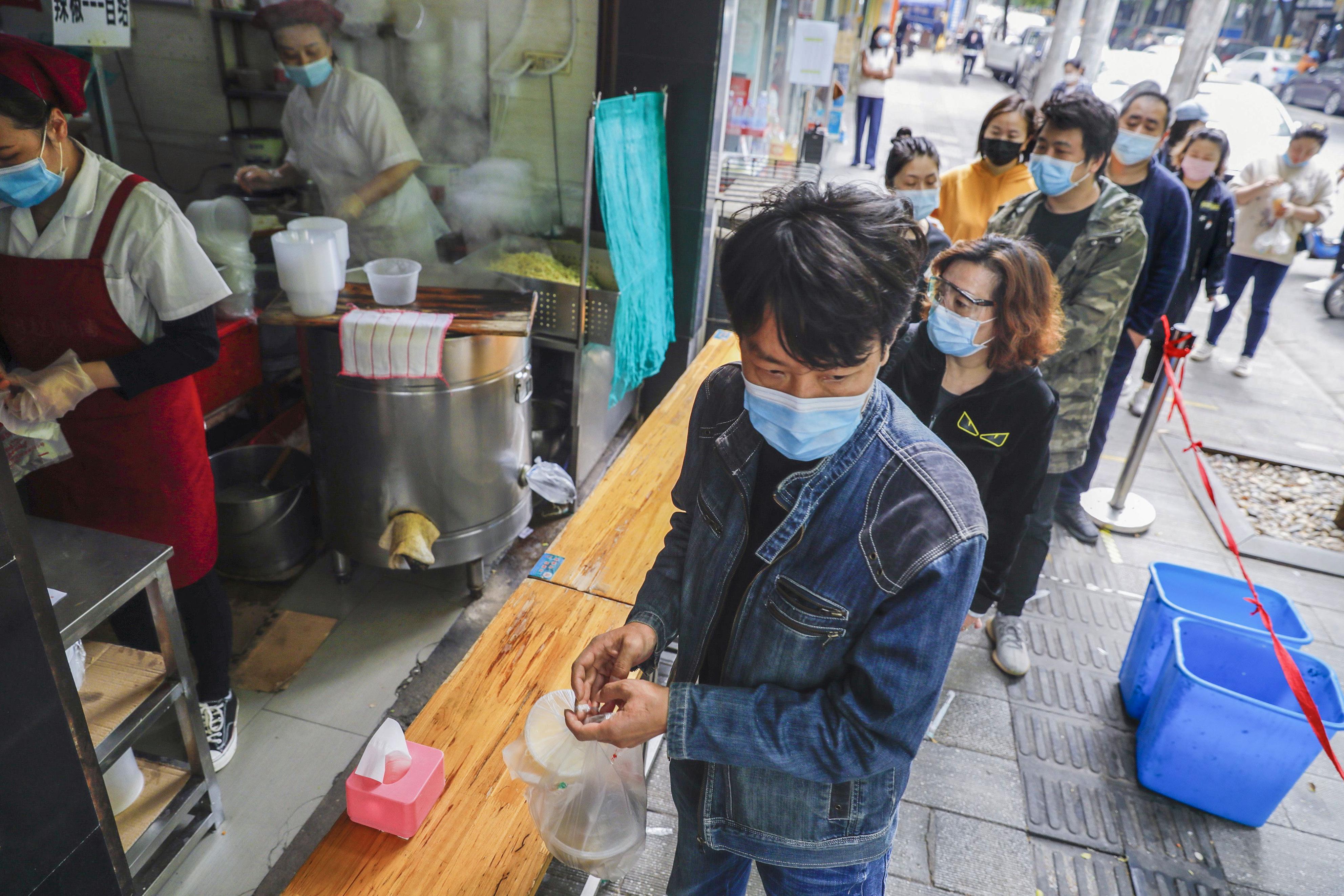 飲食店の前に列を作る市民ら=22日、中国・武漢(新華社=共同)