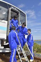 緊急停止した列車の先頭車両からはしごを使って避難する乗客役の訓練参加者=19日午前、岩手県洋野町