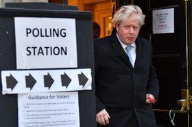 12日、英国下院の総選挙で投票所を出るジョンソン首相=ロンドン(ロイター=共同)