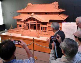 本物の10分の1サイズの首里城正殿模型を見学する関係者ら=19日、那覇市の県立博物館・美術館
