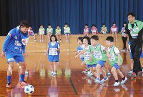 脇本晃成選手(左)とサッカーを楽しむ児童たち=滑川市東加積小で