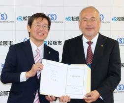 【協定書を示す濵口社長(右)と竹上市長=松阪市役所で】