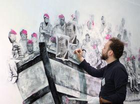 ボートに乗った各国の首脳を描くシリア人の男性アーティスト=2月、韓国・江陵(共同)