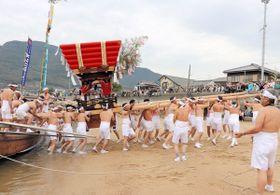 秋祭りで奉納する太鼓台を船で運び、浜に担ぎ上げる「オシコミ」=小豆島町池田