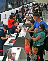 新しくできた連結ターミナルで搭乗手続きをする利用客ら=18日、那覇空港(国吉聡志撮影)