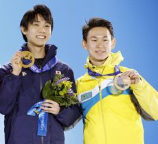 2014年2月、ソチ五輪フィギュアスケート男子の表彰式で、金の羽生結弦選手の横で銅メダルを掲げるデニス・テン選手(右)(共同)