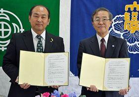 協定書に署名、調印した山本町長(左)と佐藤学長