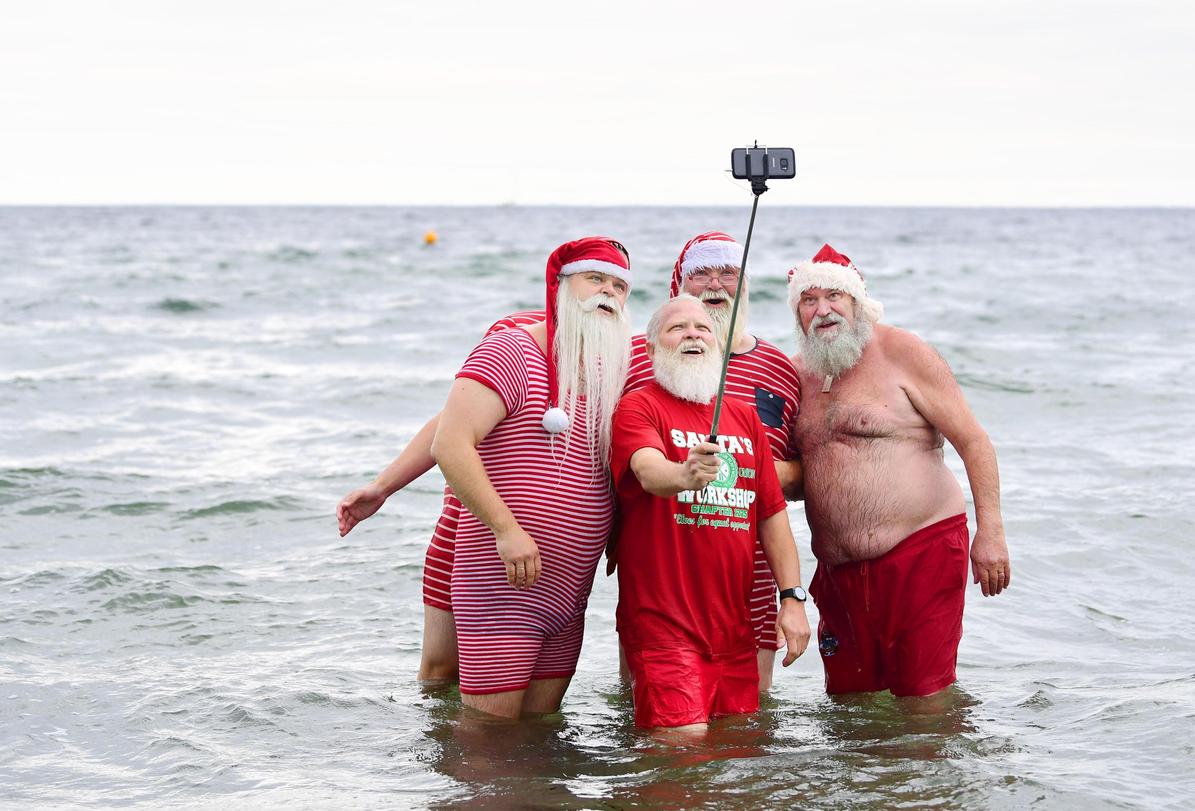 海に入り、記念撮影を楽しむ水着姿のサンタたち=コペンハーゲン郊外(撮影・仙石高記、共同)
