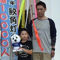 本年度1万人目の来場者となった伊賀七翔君(左)と父の大貴さん