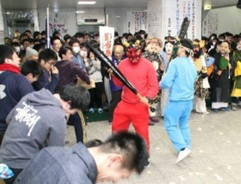鬼に扮した留学生に向けて豆をまく北九州予備校の生徒たち