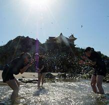 照りつける太陽の中、砂浜で水を掛け合ってはしゃぐ女子学生たち=25日午後3時23分、八戸市の蕪島海水浴場