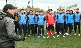練習前、片野坂監督(左端)の話を聞くトリニータの選手たち=県サッカー協会スポーツ公園