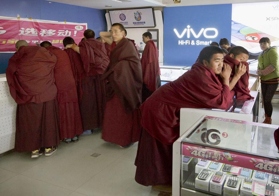 携帯電話の販売店で商品に見入る若い僧侶たち。厳しい勉強の日々の中で唯一の娯楽のようだ=中国・四川省(撮影・高橋邦典、共同)