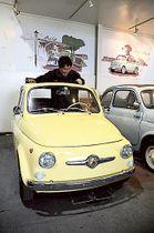 ルパン三世ファンの依頼で「フィアット500」を修復した平井秀一さん。エンブレムはアニメ第4シリーズに登場する車を再現した=17日午後、静岡市駿河区の「スティルベーシック」