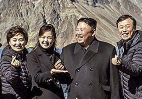 中朝国境にある白頭山を訪問し、指でハートの形を作って記念写真に納まる北朝鮮の金正恩朝鮮労働党委員長(中央右)と李雪主夫人(同左)=20日(韓国大統領府提供・共同)