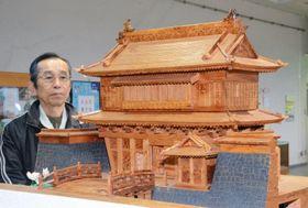御楼門の模型と制作した堀切篤行さん=日置市中央公民館