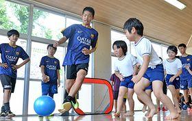 サッカー教室で園児とボールを蹴る選手=島根県隠岐の島町西町