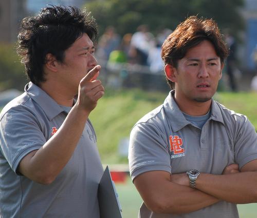 ハーフタイムに真剣な表情で話す田中さん(左)と木目田さん=神奈川県大会決勝、8日、川崎球場